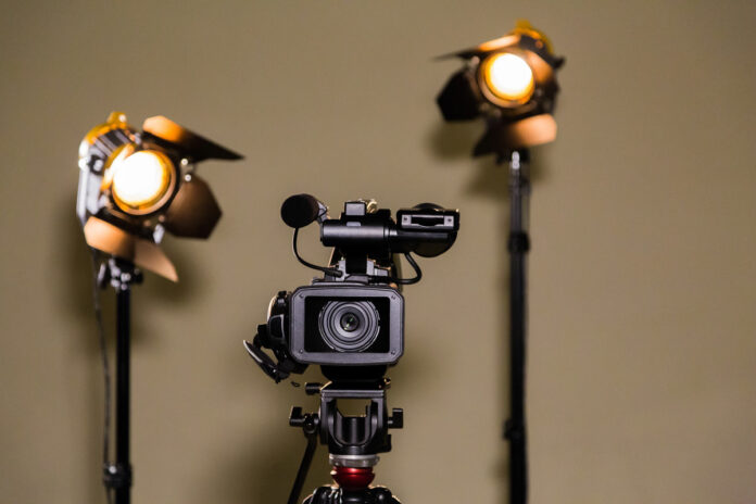 Video camera and lighting equipment against brown wall