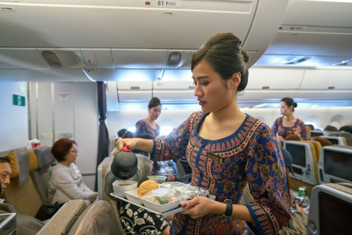 Singapore airlines air hostess pouring coffee for passenger