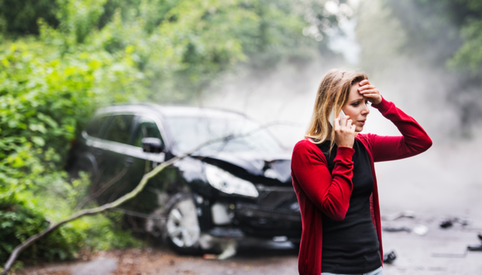 Young blonde lady on phone with crashed car in background