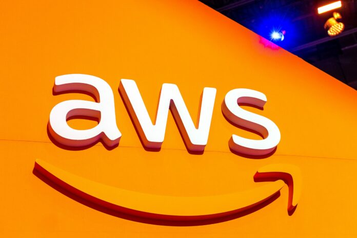 AWS logo on an orange wall with blue light shining over the top corner