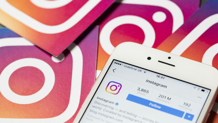 Smartphone on Instagram app screen with Instagram logo stickers in background
