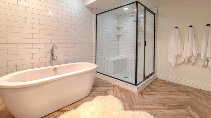 Bathroom with bathtub and framed shower