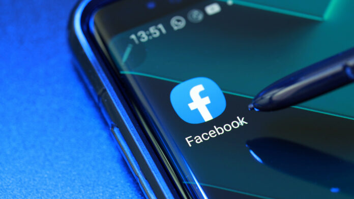 Smart phone with stylus showing Facebook application logo