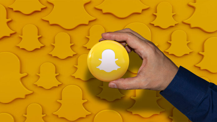 Person holding yellow ball with Snapchat logo on ball and in background